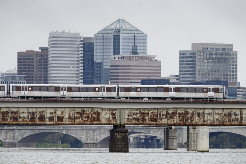 A Washington Metro train crosses the Potomac River with the skyline of Roslyn, Va., in the distance
