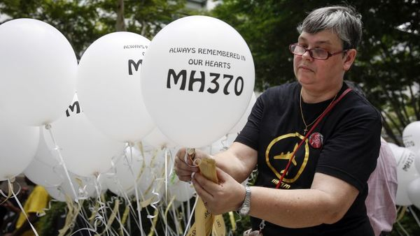Jacquita Gomes, wife of Patrick Gomes, the in-flight supervisor on the ill-fated Malaysia Airlines Flight 370, prepares balloons with names of those on board during a remembrance event in Kuala Lumpur, Malaysia, Sunday, March 6, 2016. (AP Photo/Joshua Paul)