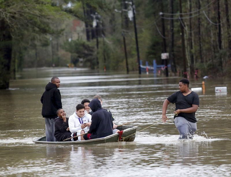 Zavion Watson, right, pulls a boat full of relatives to dry land Friday, March 11, 2016, as they evacuate their homes on West Fontana Road in Independence, La.