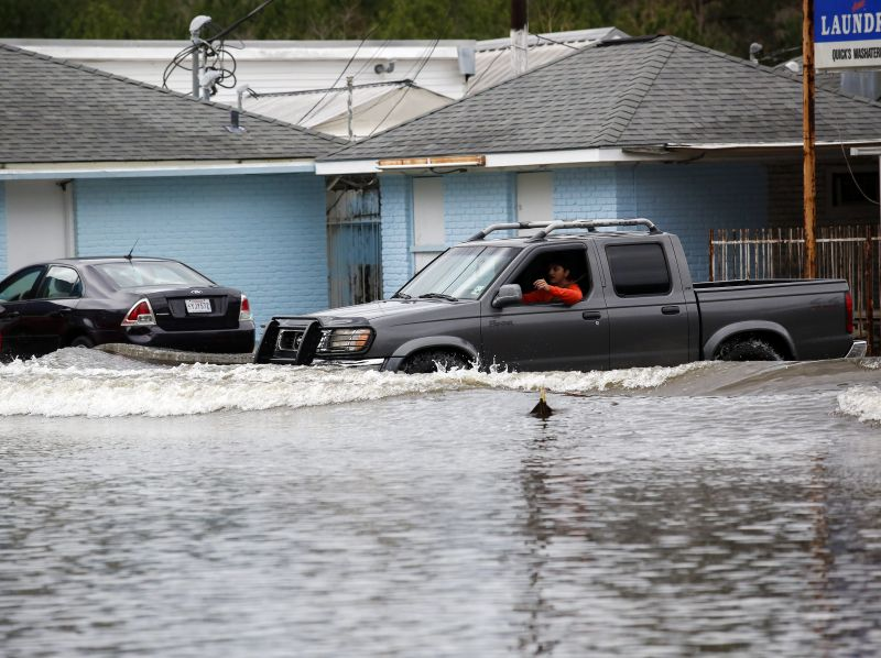 A motorist drives through flood waters in Hammond, La., Friday, March 11, 2016.