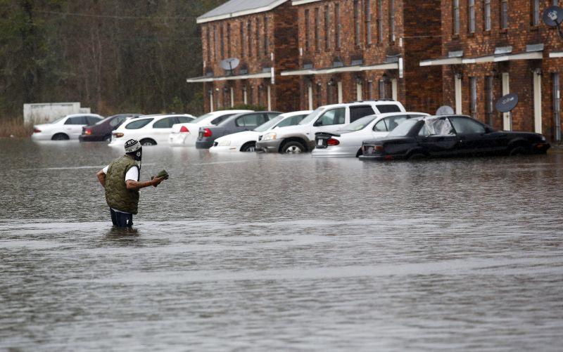 A man wades through flood waters in Hammond, La., Friday, March 11, 2016.