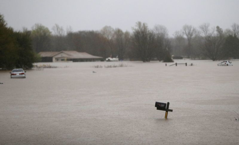 A mailbox, house and partially submerged cars are seen in rising floodwaters in Bossier Parish, La., Thursday, March 10, 2016.