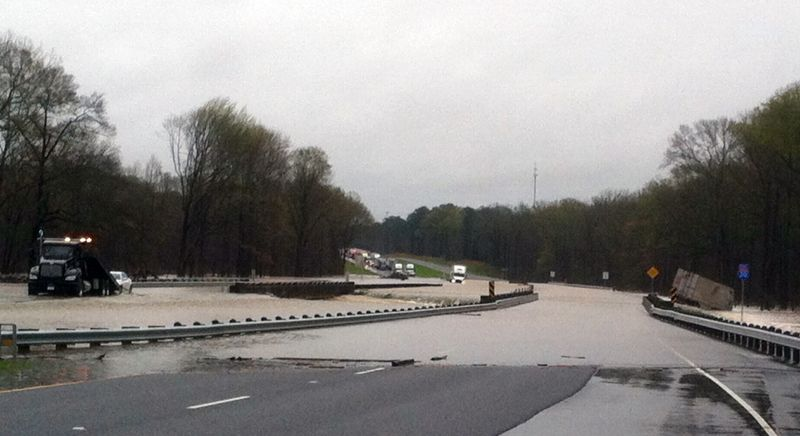 vehicles lie in flood water, Wednesday, March 9, 2016, on Interstate-20 near the 55 mile marker near near Dubberly, La.
