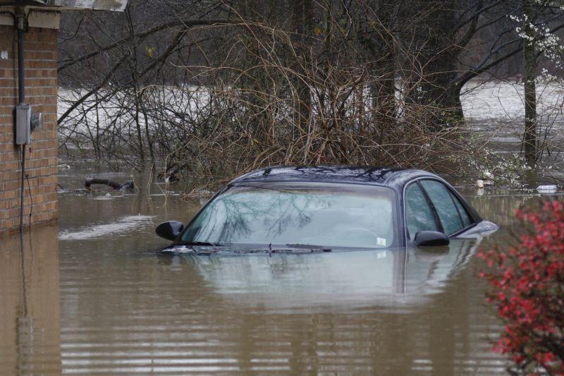 A sedan sits underwater along Shaw Street in Drew, Miss., Friday, March 11, 2016