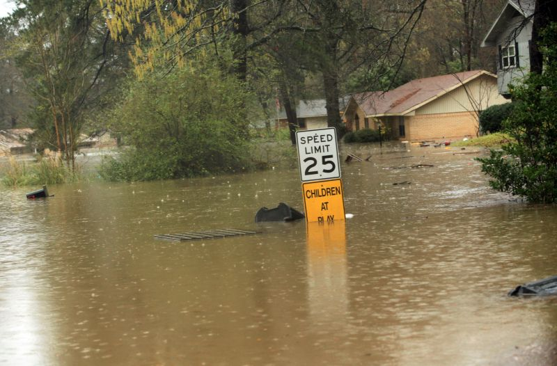 A speed limit sign is nearly covered by floodwaters in the Tall Timbers Haughton, La, subdivision Wednesday, March 9, 2016.