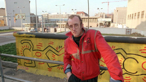 In this October 1986 file photo, artist Keith Haring stands in front of part of the Berlin Wall that he painted with a crawling baby in Berlin. The Berlin Wall came down in late 1989. Haring died of AIDS Feb. 16, 1990, at age 31.(Photo: Elke Bruhn-Hoffmann/AP Photo)