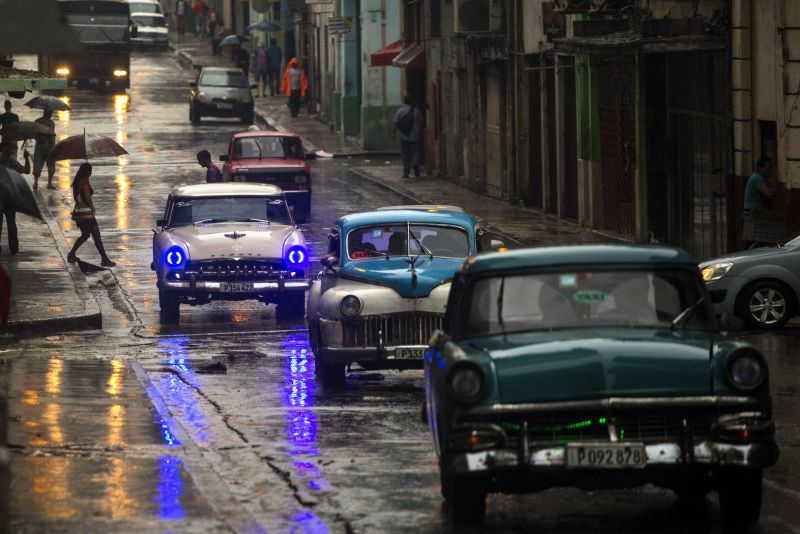 Cars drive along Neptuno Street as it rains in Havana, Cuba