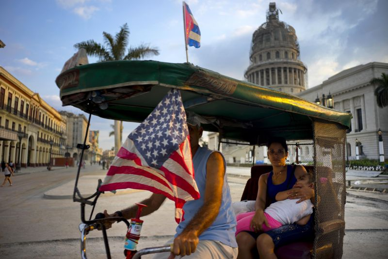 A taxi pedals his bicycle, decorated with Cuban and U.S. flags, as he transports a woman holding a sleeping girl, near the Capitolio in Havana, Cuba, Tuesday, March 15, 2016.  (AP Photo/Ramon Espinosa)