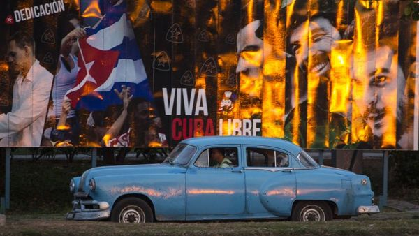 A taxi driving a classic American car passes a billboard that reads in Spanish:
