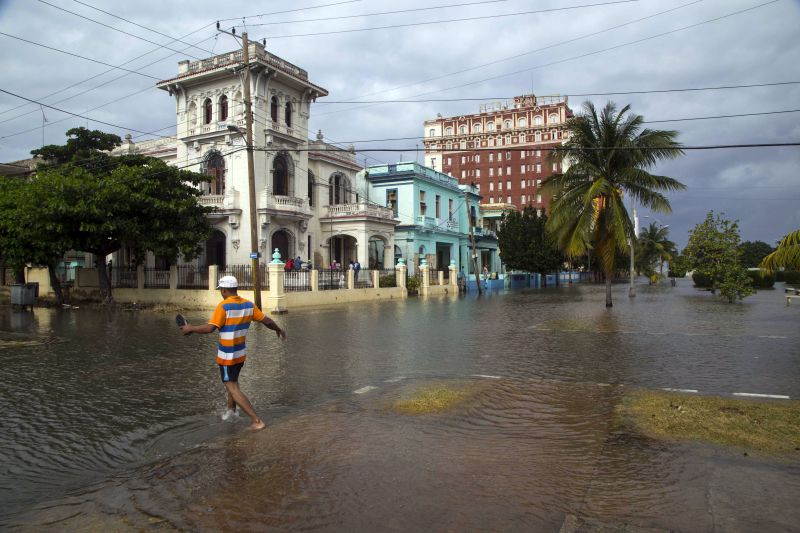 A pedestrian wades through a flooded portion of Avenida de los Presidentes, in Havana, Cuba, Saturday, Jan. 23, 2016.