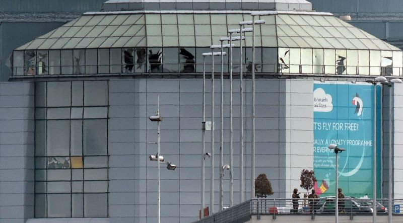Soldiers from the Belgian Army patrol in front of broken windows at Zaventem Airport in Brussels after an explosion