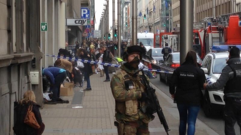 In this image taken from TV an armed member of the security forces stands guard as emergency services attend the scene after a explosion in a main metro station in Brussels