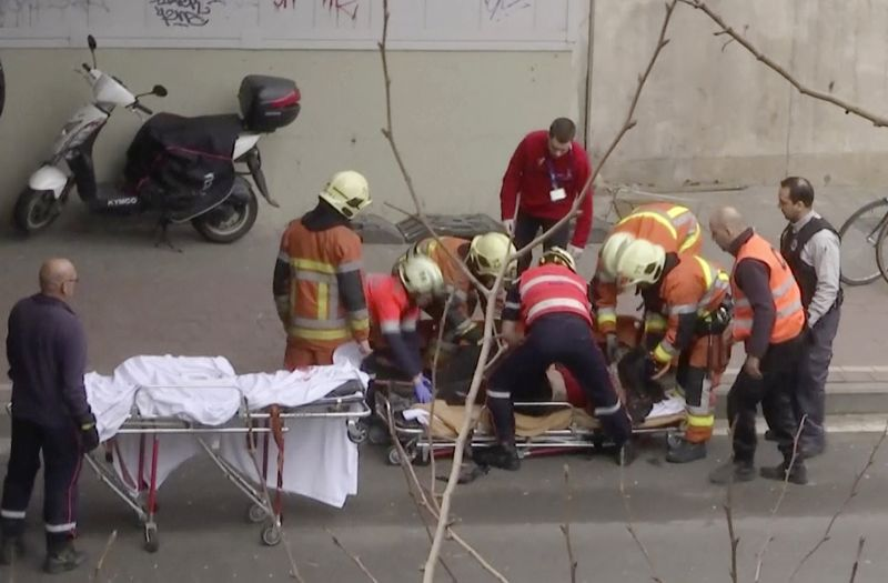 emergency rescue workers stretcher an unidentified person at the site of an explosion at a metro station in Brussels, Belgium