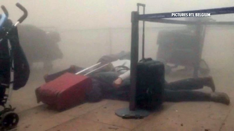 Travelers lie on the floor in a smoke filled terminal at Brussels Airport, in Brussels after explosions