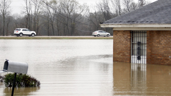 Traffic rushes past this flooded neighborhood in Drew, Miss., on March 11 as floodwaters affected areas in the Delta after a large amount of rain. (Photo: Rogelio V. Solis/AP Photo)