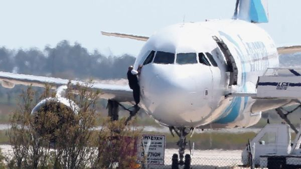 A man leaves the hijacked aircraft of Egyptair from pilot window at Larnaca airport in Cyprus Tuesday, March 29, 2016. An Egyptian man hijacked an EgyptAir plane Tuesday and forced it to land on the island of Cyprus, where all passengers and crew were eventually freed and he himself was arrested, Egyptian and Cypriot officials said. The hijacker had kept four crew members and three passengers on board, but TV footage later showed several people disembarking from the aircraft and a man who appeared to be a crew member climbing out of the cockpit window. (AP Photo/Petros Karadjias)