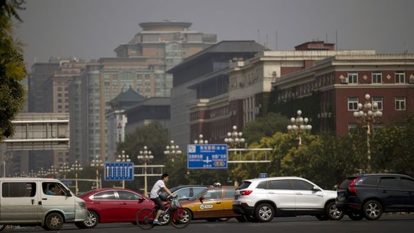 A cyclist rides past busy traffic and government administrative buildings on Chang'an Avenue in Beijing Sunday, July 12, 2015. (AP Photo/Andy Wong)