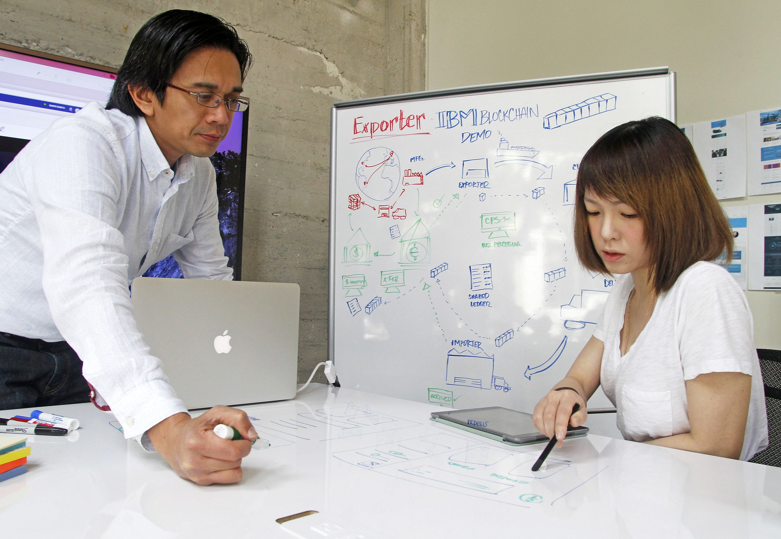 IBM Blockchain user interface designers, Dante Guintu, left and Andrea Lee, work on secure blockchain apps