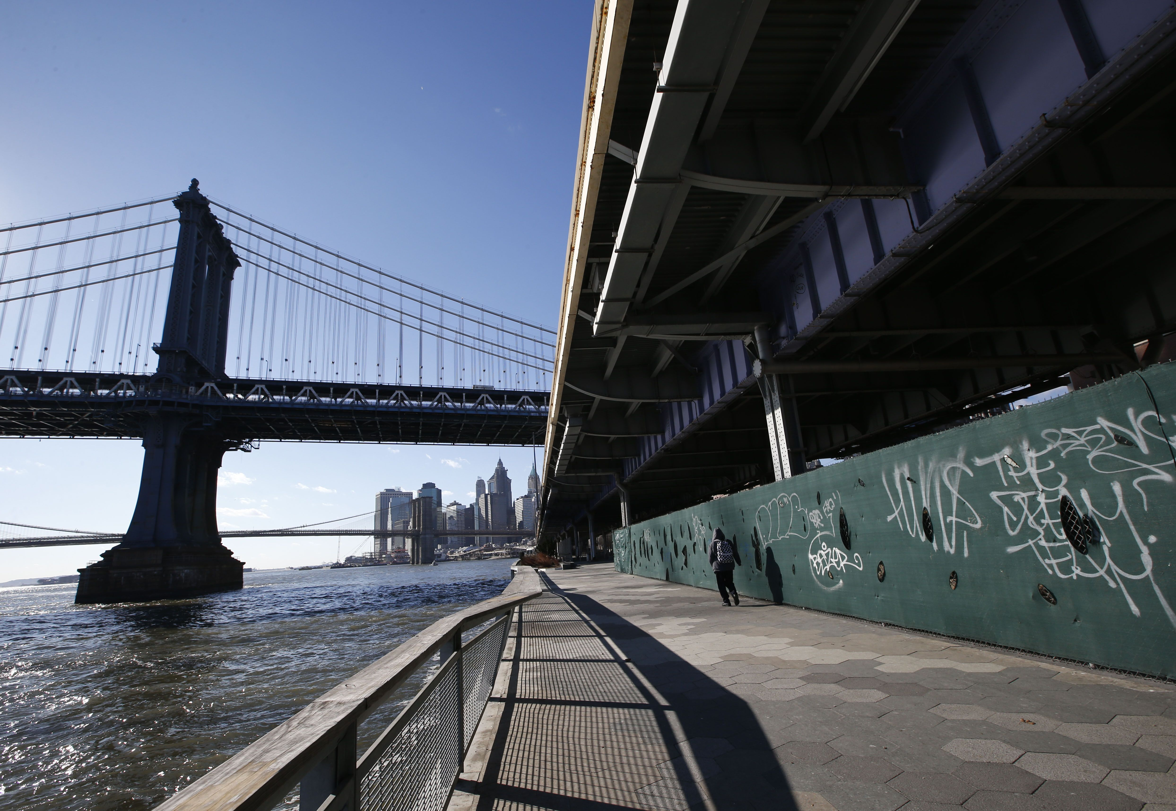 A pedestrian walks along the East Side Esplanade in an area beneath the FDR drive just north of the Manhattan Bridge