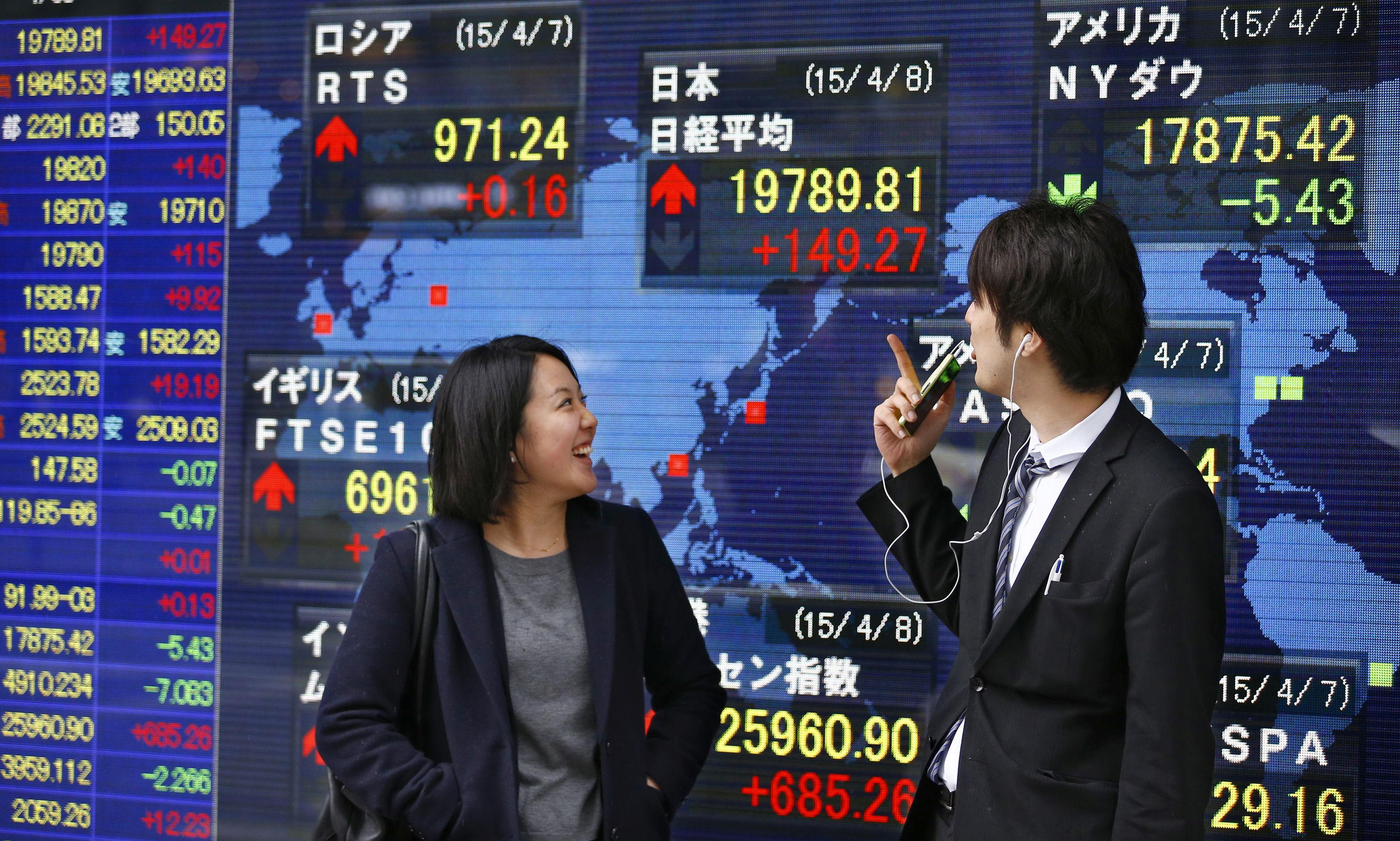 People check an electronic stock indicator of a securities firm in Tokyo