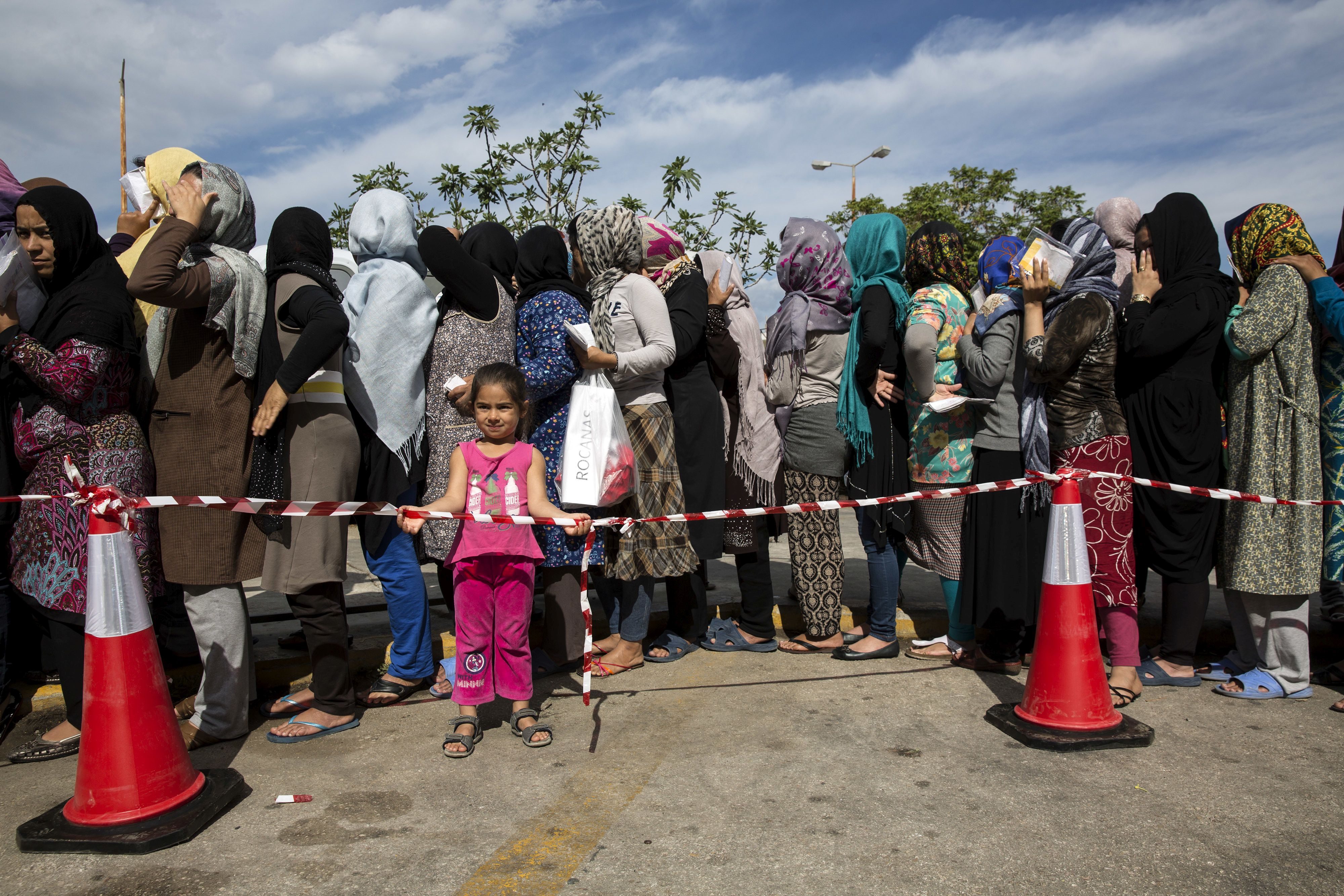 Women queue as they wait for distribution of hygiene kits