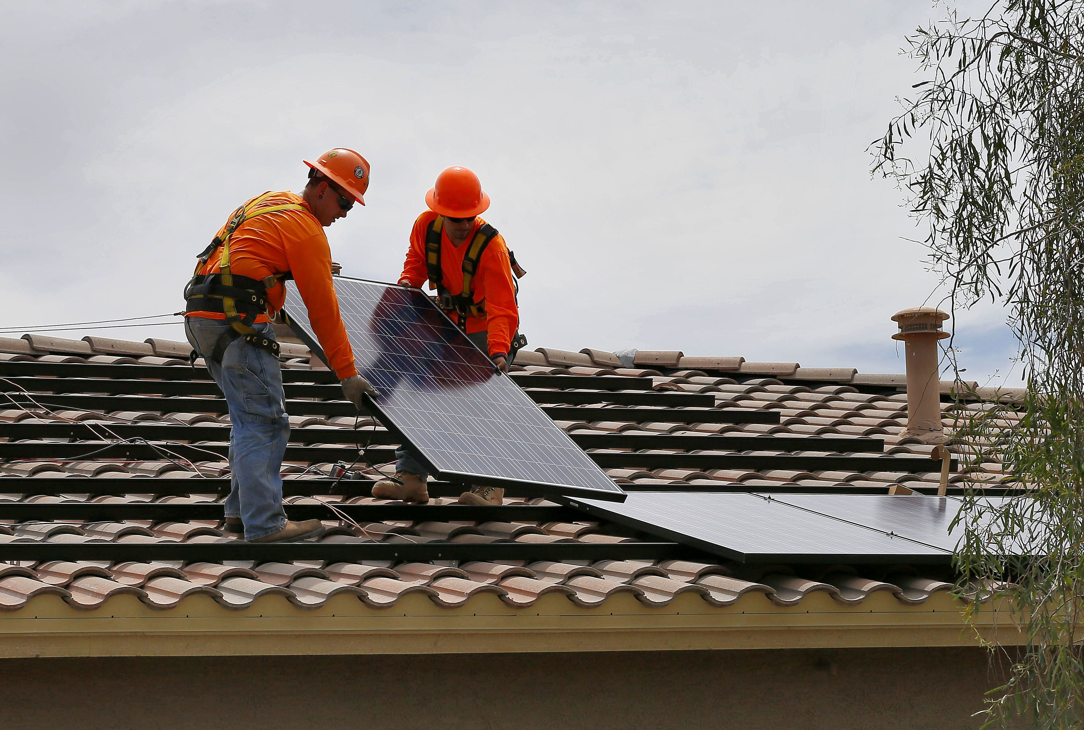 electricians Adam Hall, right, and Steven Gabert, install solar panels on a roof for Arizona Public Service company in Goodyear, Ariz.