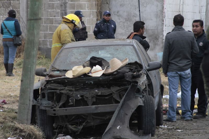 Hats belonging to victims sit on the hood of a damaged car