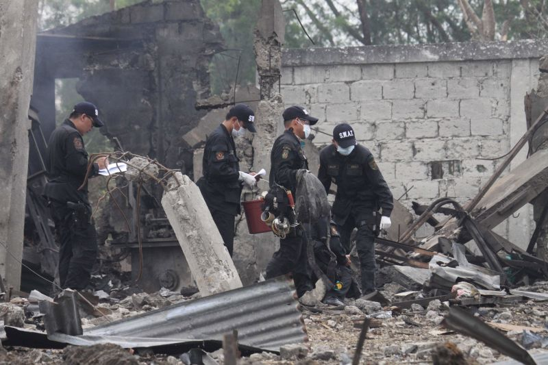 Police investigators gather pieces of evidence at the site Friday Jan. 30, 2009, a day after a powerful explosion at a fireworks factory