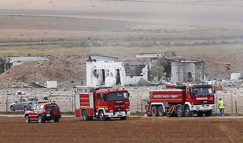 The destroyed fireworks factory Pirotecnia Zaragozana's building is seen behind firefighters trucks