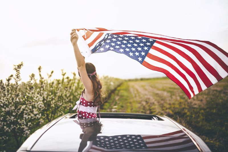 Girl holding an American flag out car sunroof in the wind