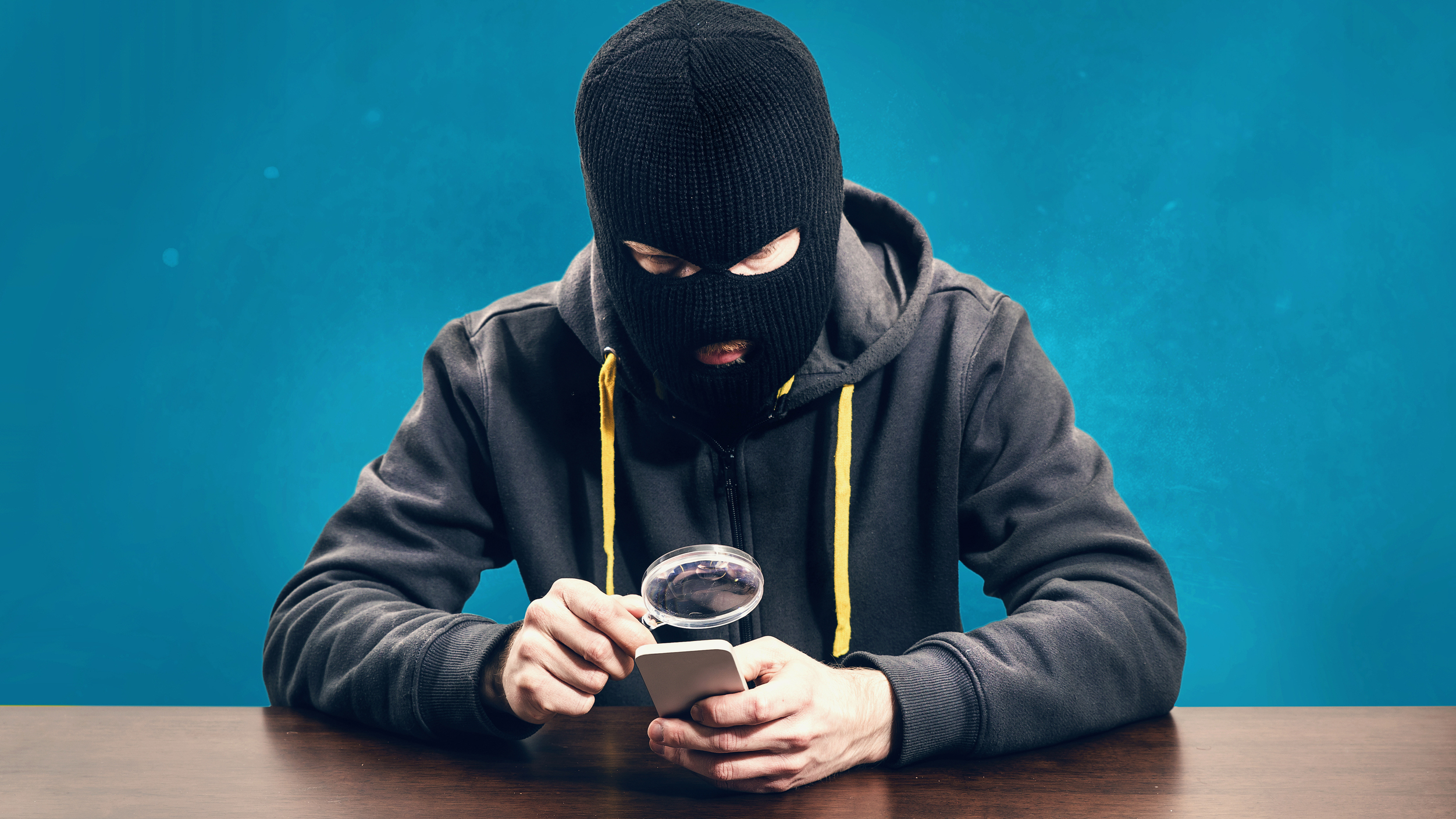 Hacker-inspecting-smartphone-with-magnifying-glass-iStock