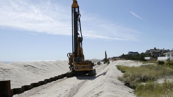 In this photograph taken Thursday, Oct. 9, 2014, workers labor on the new seawall which will protect Mantoloking, N.J., from the Atlantic Ocean during storms.  (AP Photo/Julio Cortez)