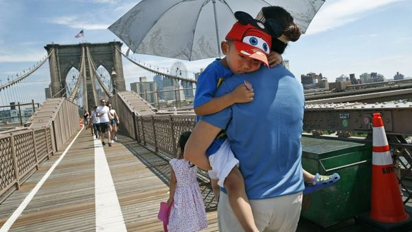 Xiuquin Huang carries her grandson Ruize Yan beneath an umbrella as she walks across the Brooklyn Bridge with her daughter and granddaughter Rina Wu, as excessive heat continued to blanket the Northeast on July 24. (Photo: Kathy Willens/AP Photo)