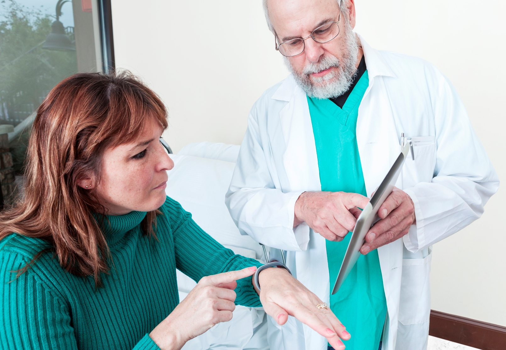 Patient with wearable device talking to doctor with tablet