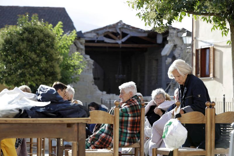 Residents sit outdoors following an earthquake in Cumuli, central Italy