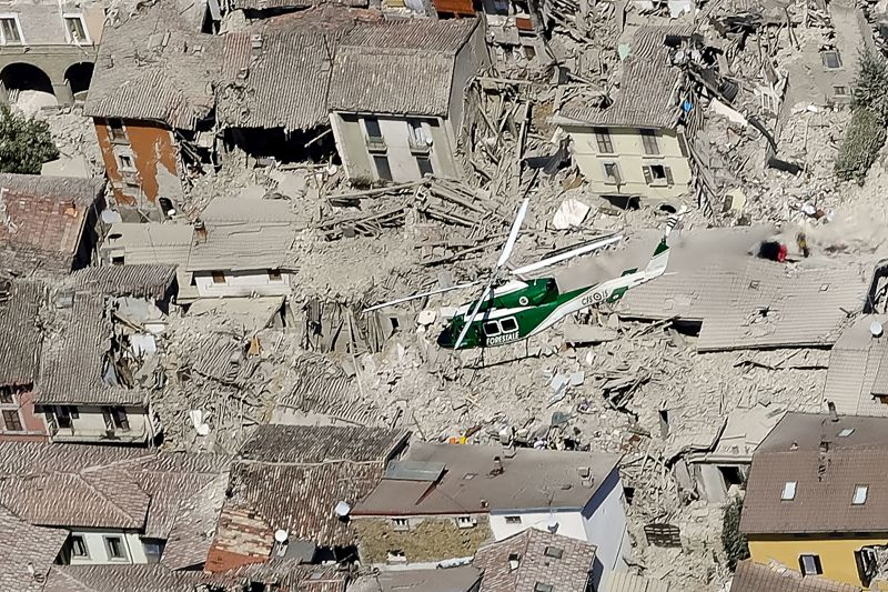 rescue helicopter flies over earthquake rubble