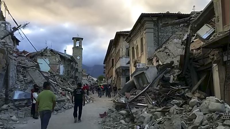 people walking amid earthquake debris