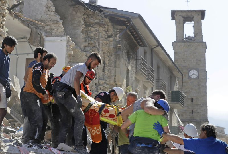 victim is carried on a stretcher from a collapsed building