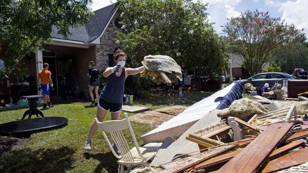 Hannah McLain, 22, a volunteer organized by a local Baton Rouge church, helps throw out waterlogged items from the home of Rhonda Brewer in Baton Rouge, La., Tuesday, Aug. 16. (Photo: Max Becherer/AP Photo)