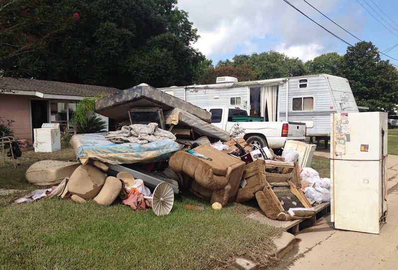 debris sits outside the flood-ravaged home of Carolyn and James Smith in Denham Springs, La.