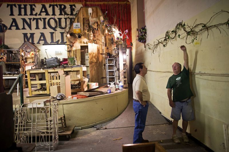 Denham Springs Mayor Gerard Landry, left, listens to Theatre Antiques Mall owner, Elvin Watts, tell him how high the water reached in his business