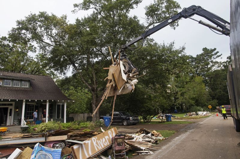 debris from gutted home is taken away in Denham Springs, La.