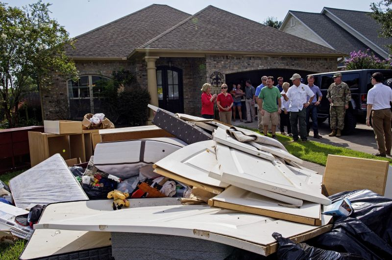 Louisiana Gov. John Bel Edwards, right, tours a flood damaged home in Youngsville, La.