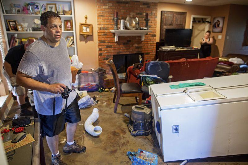 Raymond Lieteau takes photos his flood damaged hom