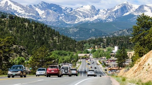 The road leading into Estes Park, Colorado, with traffic and snowcapped Rocky Mountains in the background. (Photo: iStock)