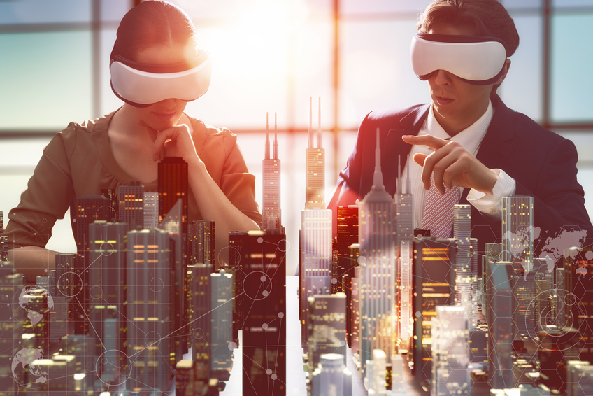 Two business people wearing virtual reality glasses looking at 3d model of buildings