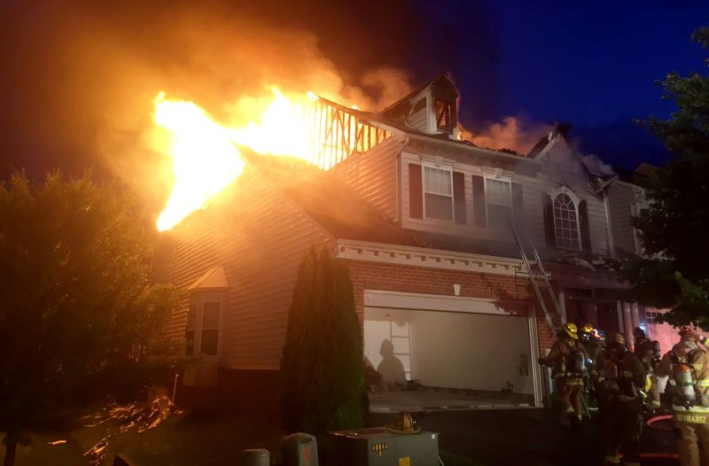 firefighters work to contain a single family house fire