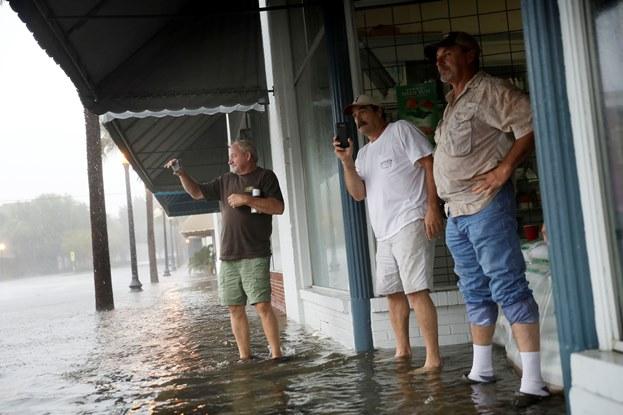 3 men taking pictures flooded street Hurricane Matthew