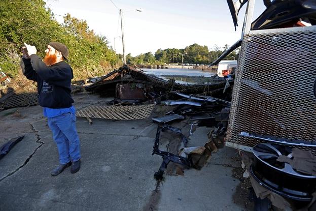 Employee taking photos damaged business Hurricane Matthew