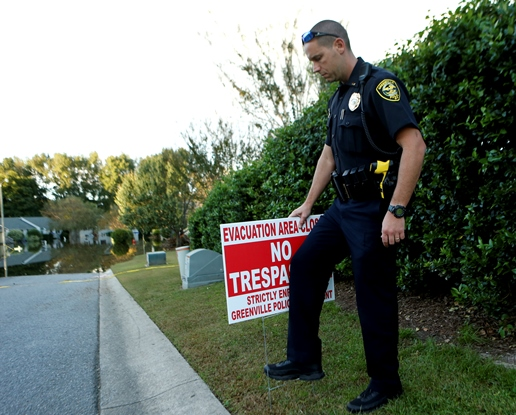 Police officer with evacuation no trespassing sign flooded street